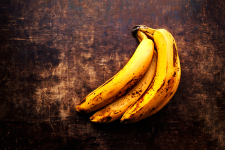 bad banana: Very ripe banana close up - A branch of rotten ripe bananas on vintage wooden background.