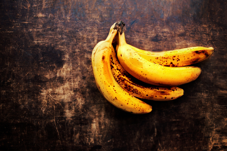 bad banana: A branch of rotten ripe bananas on vintage wooden background.