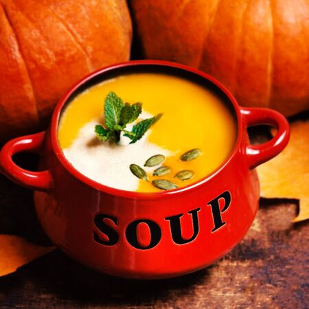 swirled: Bowl of pumpkin soup swirled with coconut cream with fresh pumpkins and bread crouton on wooden table.