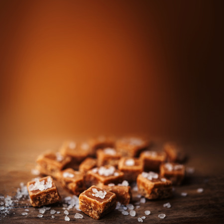 Salted caramel pieces and sea salt close up, top view. Butterscotch toffee caramel with copyspace