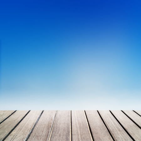 Old vintage brown wood panel tabletop with  Abstract  blur natural blue sky gradient backdrop wall. View with copy space