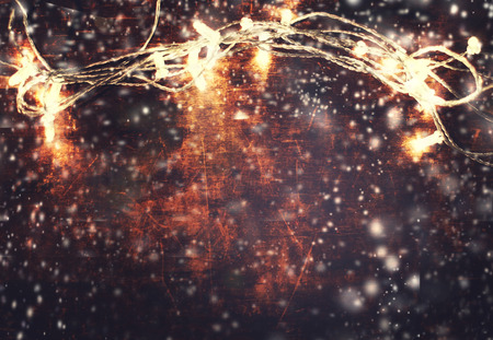 christmas backdrop: Christmas and  New Year card - wooden background with christmas lights garland and falling snowflakes. Christmas lights backdrop with empty copy space. Stock Photo