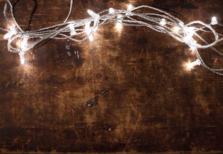Luces de Navidad sobre fondo de madera. Luces festivas, guirnaldas. Decoraciones de navidad