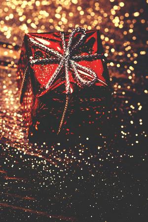 Christmas card with ornament, red present and golden sparkling lights Reklamní fotografie