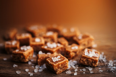 Toffees. Salted caramel pieces and sea salt close up, top view. Butterscotch toffee caramel