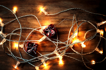christmas backdrop: Christmas background, greeting card with festive  lights on dark wooden backdrop, close up. Merry Christmas lights garland Stock Photo