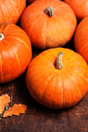 wood carvings: orange pumpkins over wooden table with copyspace