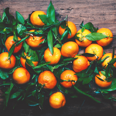 Tangerines with leaves on wooden background. Mandarins Tangerine Closeup. Rustic style Stock Photo