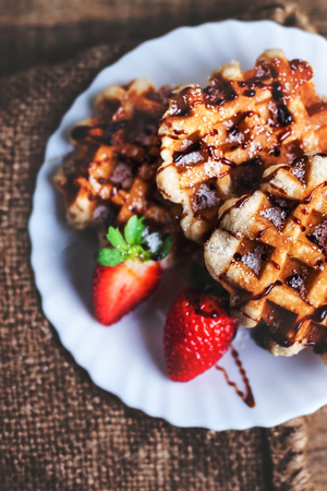 Belgian waffles topped with strawberries, syrup and icing. Homemade breakfast in rustic style, toned image with copy space   Stock Photo