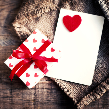st valentin: Valentines day Card with gift boxes and  hearts, blank white card for messaage  and red hearts on dark wooden background  Stock Photo