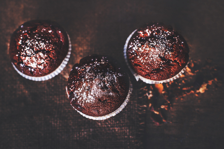 choco chips: Chocolate dark muffins on wooden table  close up, selective focus