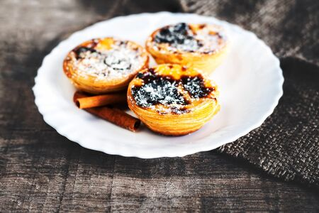 Egg tart  - creamy sweet curstard on white plate on wooden table close up with copy space. Pasteis de Belem dessert Banco de Imagens