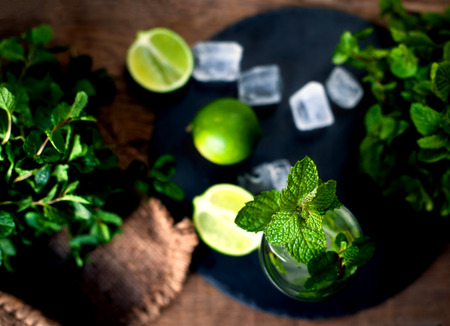 Fresh mojito drink with lime and mint in a glass on black stone board and wooden rustic table Stock Photo