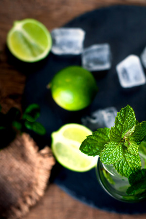 daiquiri alcohol: Fresh mojito drink with lime and mint in a glass on black stone board and wooden rustic table
