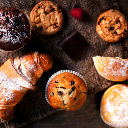Delicious Chocolate muffins, croissants and dark chocolate pieces on wooden table - Food background Stock Photo