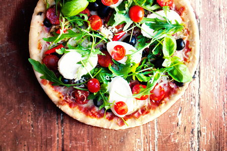 Hot pizza with meat, basil and mozarella cheese on a dark background, top view. Pizza on the rustic wooden  table with copy space