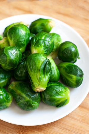 Pile of Fresh Green Brussels sprouts on a white plate on wooden table  with copy space, close up