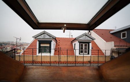 Mansard or skylight window on attic with view on red roofs and old town