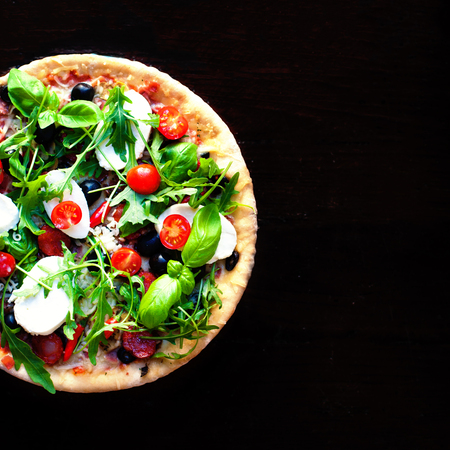 Fresh Pizza on dark background  with Copy space. Stock Photo