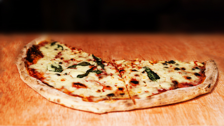 Margherita Pizza Garnished With Fresh Basil And Cheese Cutted In A Half On Stall