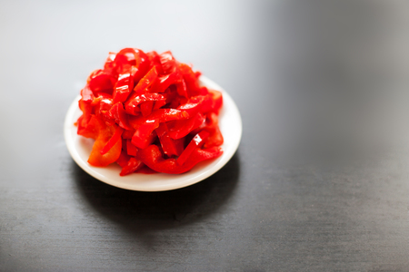 Marinated red pepper  red peppers on a plate on dark background  with copy space. Preserved red sweet chilly peppers. Canned vegetables