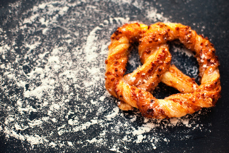 pretzel: Delicious Fresh  pastry on dark background with flour.  Sweet pretzels with powdered sugar and copyspace.  Closeup of beautiful delicious puff pastry