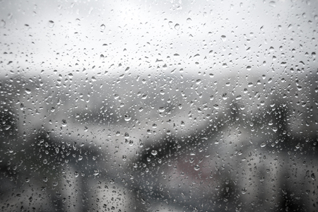Drops of rain on a black dramatic window glass background. Rain in the city. Autunm depression concept image