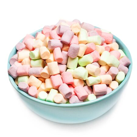 Fluffy multi colourful  marshmallows in blue round bowl isolated on white background  with copy space. Various colours marshmellows  close up. Stock Photo