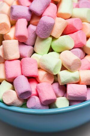 Colorful mini marshmallows in a blue bowl as background, macro. Fluffy marshmallows texture and pattern. High Resolution image, Soft focus