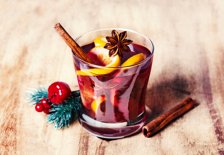 Christmas Mulled Wine for winter on wooden background. Hot wine with spices and Christmas Decorations. Traditional drink on winter holiday in rustic style Banco de Imagens - 87405470