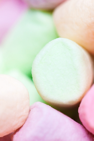 Colorful mini marshmallows background macro. Fluffy marshmallows texture and pattern. Flat lay or top view. Winter food background concept.