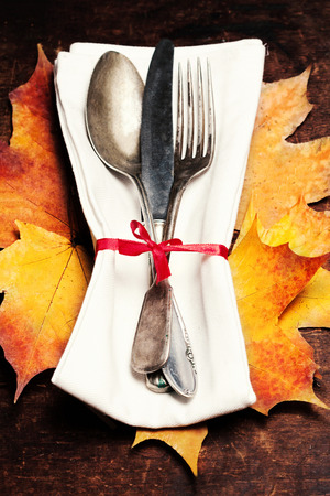 grunge cutlery: Thanksgiving table setting  -  Seasonal cutlery on rustic wooden table. Autumn holiday  background with knife, fork and spoon.
