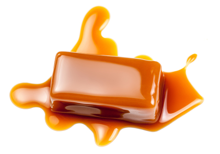 condensed: Caramel sauce flowing on caramel candies, isolated on white background. Golden Butterscotch toffee candy caramels  Stock Photo