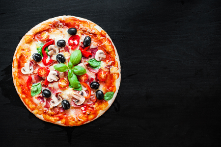 Hot pizza with Pepperoni, basil leaf on dark background  with copy space. Cheese Pizza   Stock Photo