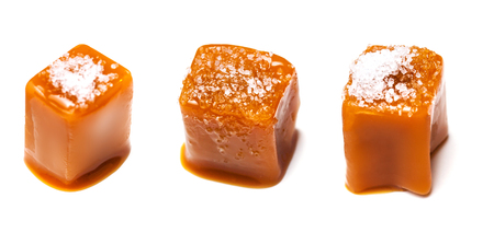 Homemade salted caramel pieces isolated on white background. Golden Butterscotch toffee candy caramels macro