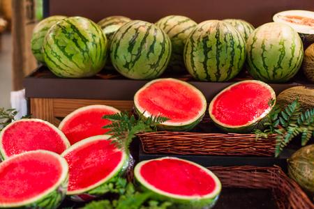 Rijpe sappige watermeloenen op een marktkraam in supermarkt. watermeloenvruchten in tweeën gesneden en heel Stockfoto - 90866879