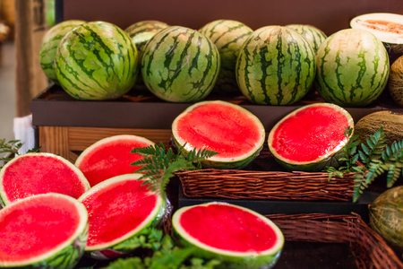 Ripe juicy watermelons on a market stall in supermarket. watermelon fruits cut in a half and whole