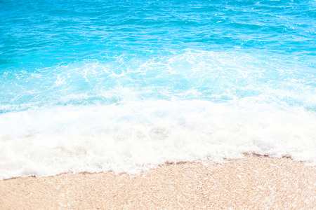 Soft wave of blue ocean on sandy beach Background with place for text. Tropical summer vacation concept.