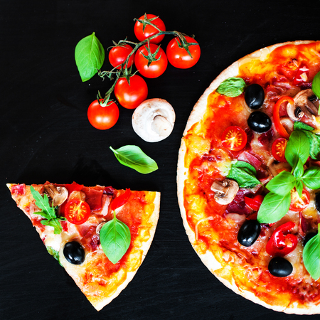 Pizza slice with Pepperoni,  Mozzarella cheese and tomatoes,  served om a black slate table board