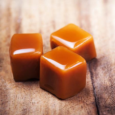 수 제 소금 된 캐 러 멜 조각 나무 배경입니다. 골든 버터 스카치 토피 사탕 카라멜과 copyspace