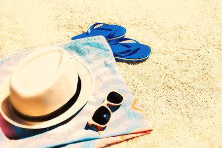 Summer fun time and accessories on a sand on the beach. Blue  sandal flip flop, hat, sunglasses and towel, vintage toned image