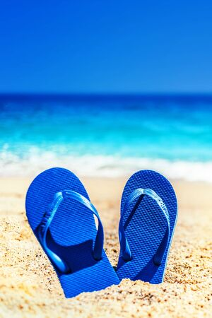 Summer fun time and accessories on a sand on the beach. Blue  sandal flip flop on the white sand with blue sea and sky in summer vacations, copy space
