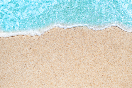Background image of Soft wave of blue ocean on sandy beach.  Ocean wave close up with copy space for text