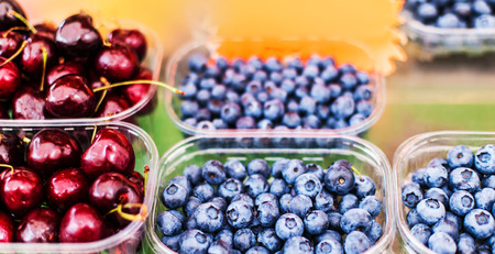 Various berries from a local farmer market.  Healthy local food market concept. Variety of berries in a box -  blackberry, raspberry, strawberry, cherry  Stock Photo