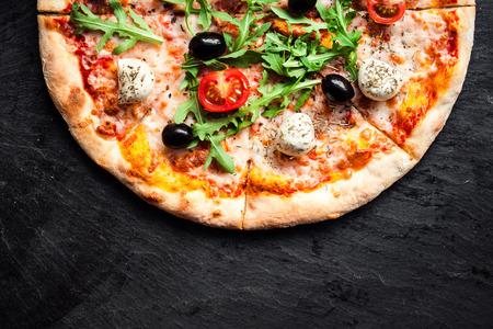 トマト、モッツァレラチーズ、ルッコラのピザ。ピザメニュー。暗い石のテーブルのコピースペースを持つトップビュー 写真素材 - 94348080