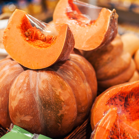 Pumpkins on a stall at organic farmers grocery store. Ripe cut in a pieces  pumpkins at market  Stock Photo