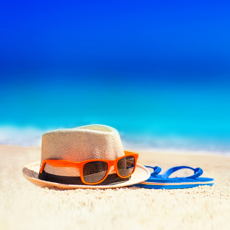 Flip-flops, beach hat, sun glasses on the sand. Summer vacation concept. Summer fun time and accessories on tropical beach, relax idea  Stock Photo