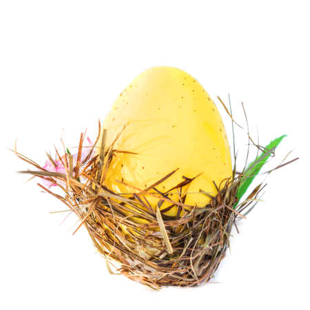 Easter eggs in a wicker nest on white wooden background with  copy space.  Festive decoration. Happy Easter!