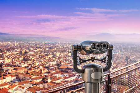 Amazing viewpoint with coin binoculars in Florence, Italy. Binoculars overlooking Florence bird view at beautiful sunset. Panorama of Florence