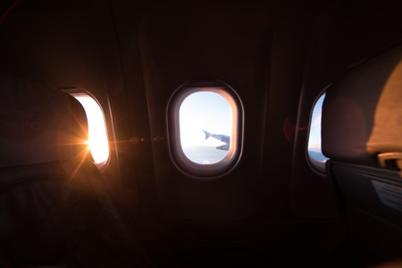 Airplane window view inside an aircraft. Window plane at sunrise with rays of morning light. Vacation destinations concept.